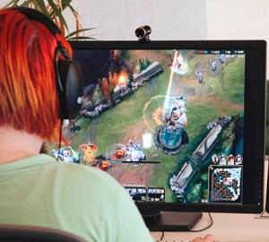 gamer vid skrivbord med två datorskärmar som streamar gameplay